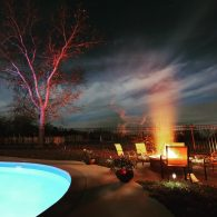 Fire pit and saltwater pool at night