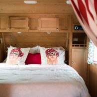 The interior of one of our camper's bedrooms. Plush queen sized beds in each camper along with beautiful bedding and pillows.